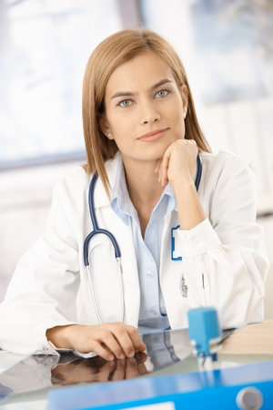 consultant physicians: Young attractive female doctor sitting at desk in office, smiling. Stock Photo