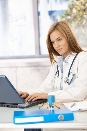 Young attractive female doctor browsing internet in office. photo