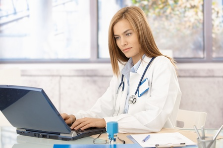 Young attractive female doctor using laptop in office, busy by working. photo