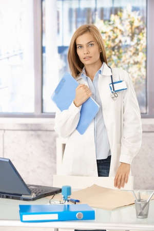 Young medical student standing in office, holding folder. photo