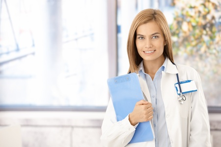 Young attractive medical student smiling in office, holding folder. photo