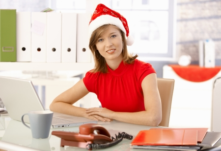Female office worker sitting at office desk, wearing xmas hat. photo