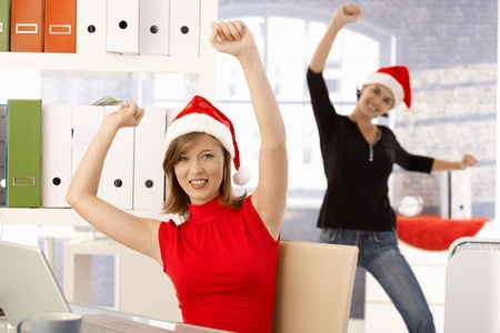 two companies: Female office workers having fun in office wearing Santa Claus hat.