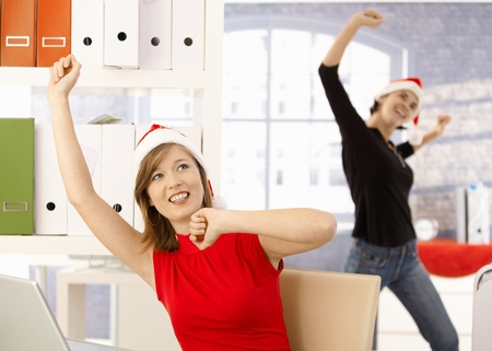 Female office workers celebrating christmas in office wearing Santa Claus hat. photo