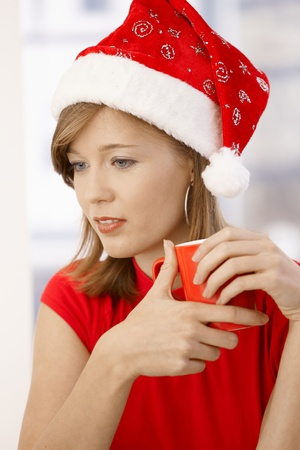 Portrait of attractive young woman, wearing red shirt and Santa Claus hat, holding cup. photo