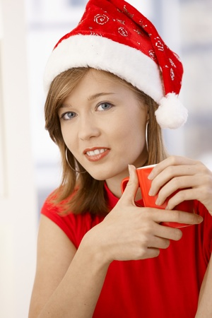 Portrait of attractive young woman, wearing red shirt and Santa Claus hat Looking at camera, smiling. photo