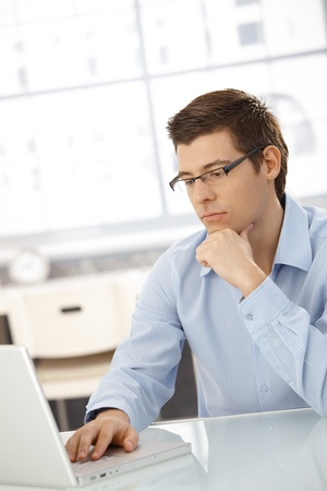 Young businessman concentrating on computer work, looking at laptop screen, thinking. Stock Photo - 8398095