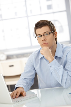 Portrait of thinking businessman sitting in office with laptop computer, looking at camera. Stock Photo - 8398096