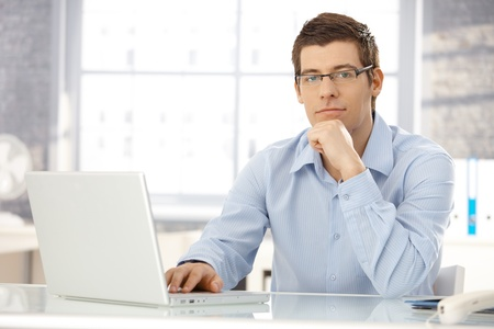 writing on glass: Portrait of office worker man sitting at office desk using laptop computer, looking at camera. Stock Photo