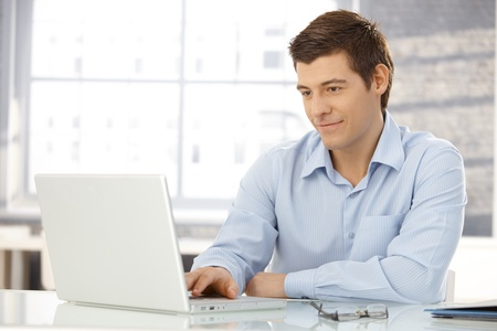 Young businessman working in office, sitting at desk, looking at laptop computer screen, smiling. photo