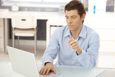 Businessman working in office on laptop computer, concentrating, looking at screen. photo