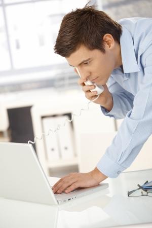 trabajador oficina: Oficina joven trabajador hombre hablando sobre el tel�fono de l�nea fija, equipo port�til, mirando la pantalla.