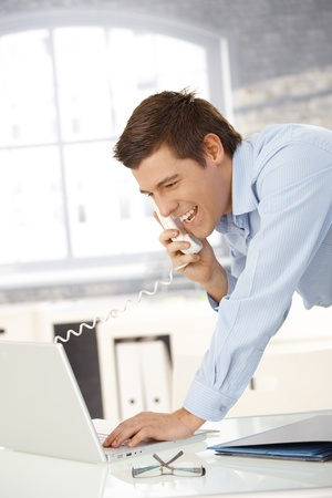 Laughing professional man on landline call with laptop computer, looking at screen. photo