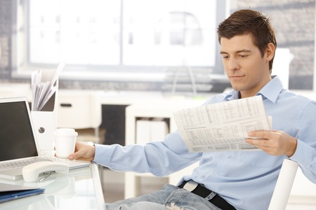 Businessman taking break in office, reading newspaper, having coffee, putting phone aside. Stock Photo - 8398132