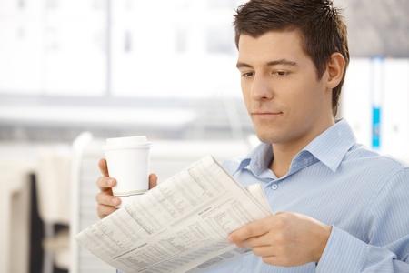 Office worker man on break reading papers, having takeaway coffee in office. photo