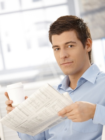 Portrait of smart young man holding coffee and newspaper in office, smiling at camera. Stock Photo - 8398115