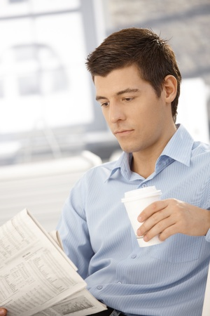 Young businessman on coffee break reading papers in office. Stock Photo - 8398158