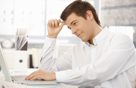 Young office worker thinking, sitting at office desk holding pen, using laptop computer, looking at screen, smiling. Stock Photo - 8398138