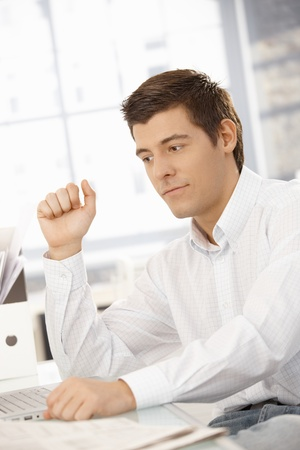 Young businessman sitting at office desk with laptop computer, thinking. photo
