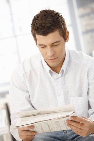 only young adults: Handsome young man concentrating on reading newspaper.