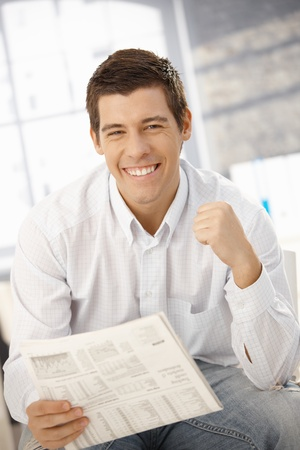 Portrait of man happy about news, smiling at camera, holding newspaper. photo