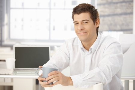 Portrait of content businessman holding tea cup, smiling happily at camera. Stock Photo - 8398097