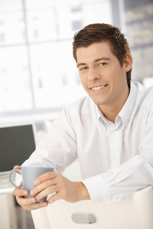 Coffee break in office, smiling businessman sitting, holding cup, looking at camera. Stock Photo - 8398099