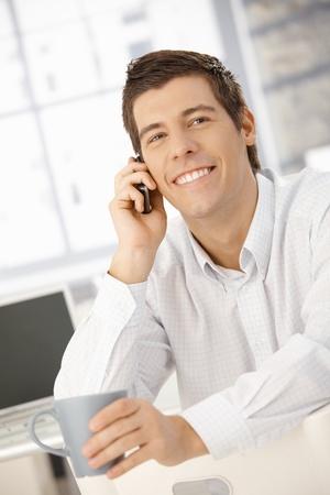 hombre sentado: Hombre de negocios feliz en llamada de tel�fono m�vil riendo, sosteniendo la taza de caf�. Foto de archivo