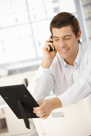 Businessman sitting in office speaking on phone, looking at photo frame, smiling. Stock Photo - 8398092