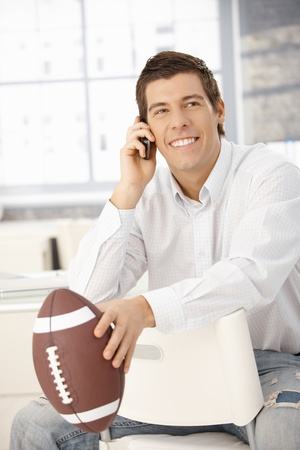 only young adults: Happy businessman sitting at desk, talking on cellphone, holding football. Stock Photo