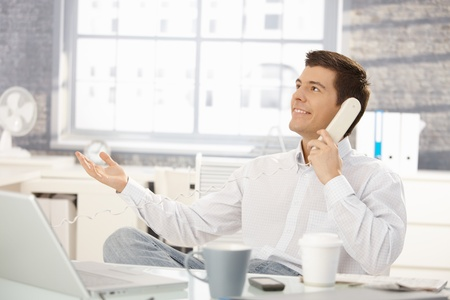 good shirt: Smiling businessman sitting at office desk on landline phone call, looking up, raising hand. Stock Photo