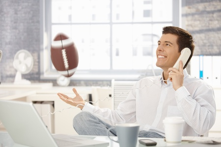 calling businessman: Businessman playing with football office while on landline call, laughing.