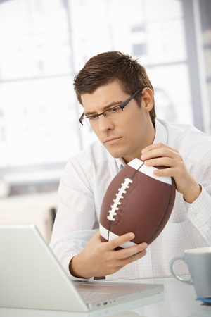 Businessman concentrating on computer work, holding football, thinking, looking at laptop screen. photo