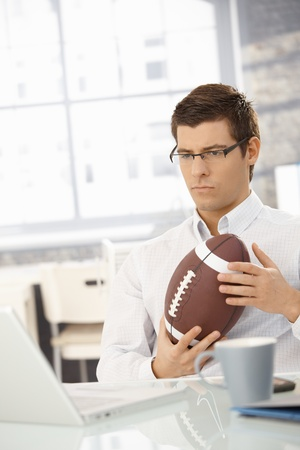 Determined businessman concentrating on work, thinking, sitting in office with football handheld. photo