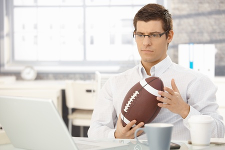 Troubled businessman thinking about work playing with football handheld in office. photo