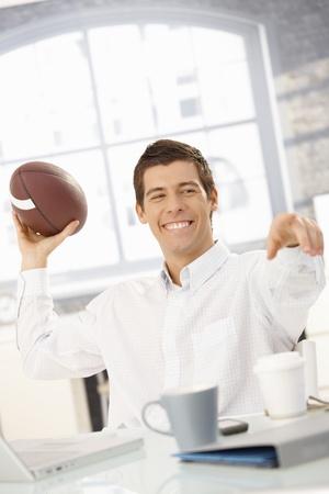 empleados trabajando: Empresario alegre sentado en la Oficina de tirar el f�tbol a colega, apuntando, riendo.