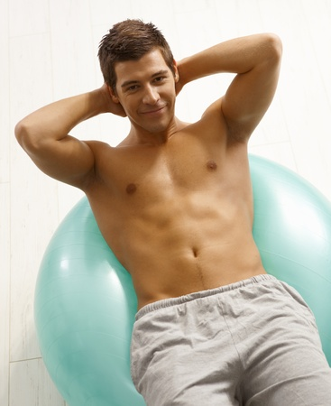 Portrait of sporty young man lying on fit ball, smiling at camera. Stock Photo - 8398105