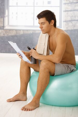Young man sitting on gym ball in break of training, drinking sports drink and checking training program on clipboard. Stock Photo - 8398152
