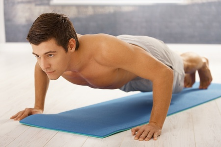 Handsome young man doing push up in gym on polyfoam mattress. Stock Photo - 8398136