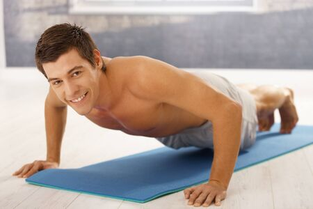 Goodlooking guy doing push up in gym, workout on polyfoam mattress, smiling at camera. Stock Photo - 8398124