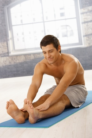Happy sporty guy stretching in gym before training, smiling. Stock Photo - 8398130