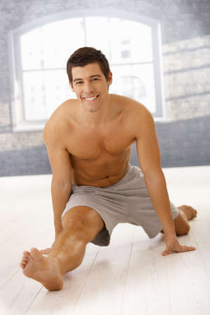 Masculine guy doing forward split in gym, smiling happily at camera. Stock Photo - 8398094