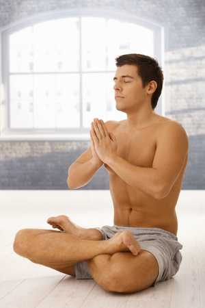 Athletic young man exercising yoga meditation in lotus posture with closed eyes. Stock Photo - 8398128