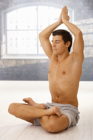 Handsome sporty guy doing yoga meditation in lotus posture with eyes closed. Stock Photo - 8398142