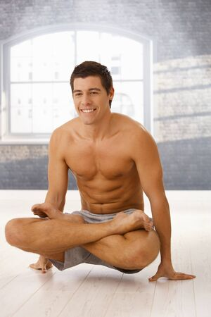 Smiling athletic guy doing yoga exercise in lotus posture in gym. Stock Photo - 8398127