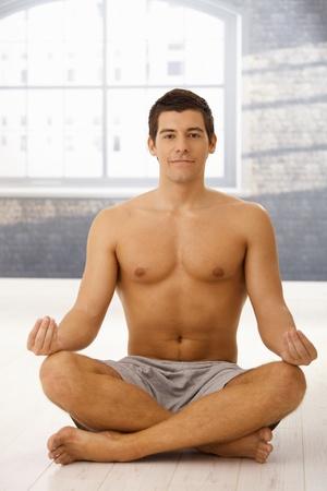 Smiling young man meditating yoga in gym, looking at camera. Stock Photo - 8398133