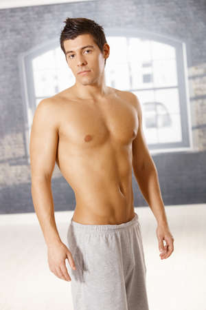 nude sport: Portrait of athletic young guy posing in gym, looking at camera.