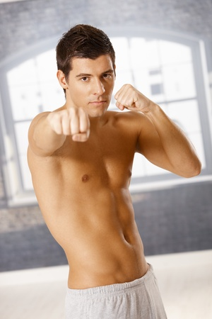 Handsome guy looking at camera in boxing pose with fist raised. Stock Photo - 8398162
