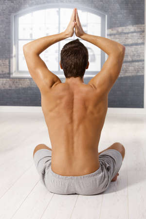 Back of muscular young man raising arms in yoga exercise, sitting on floor of gym. Stock Photo - 8398163
