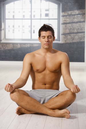 Athletic guy meditating in yoga position with eyes closed, sitting on floor. Stock Photo - 8398145